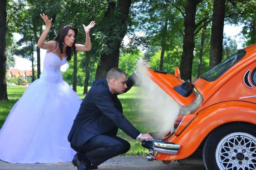 woman in white wedding gown near orange car